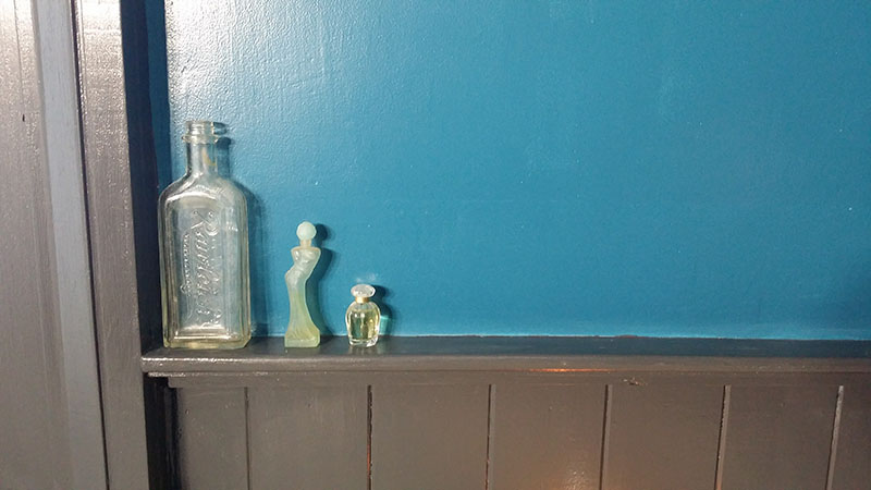 Little vintage bottles on the ledge beside the bathtub.