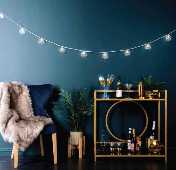 Dark teal room with gold bar cart and string lights.