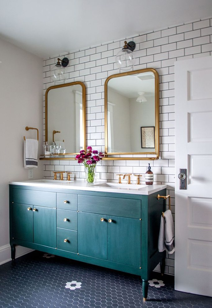 Bathroom with dark teal vanity and gold accents.