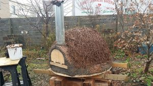 cob oven under construction slip straw insulation