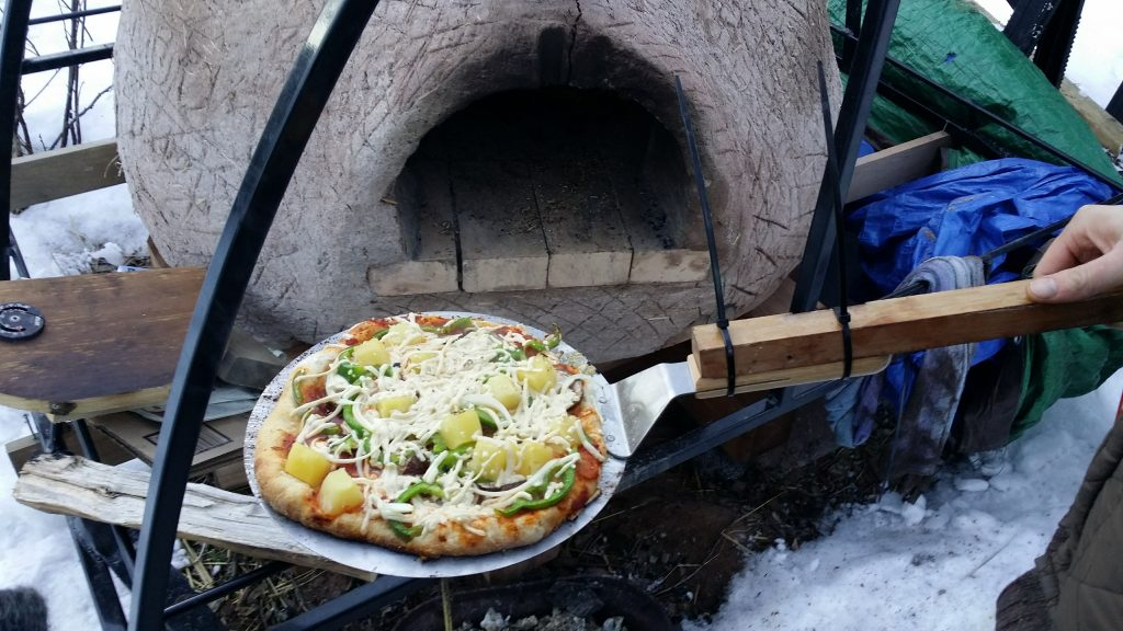 Pizza coming out of the cob oven.